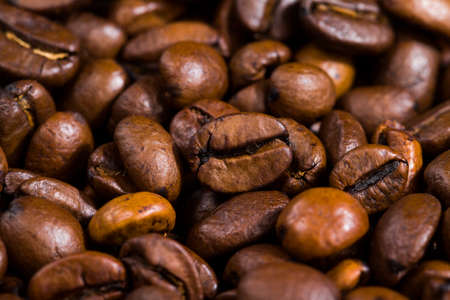 brown freshly roasted coffee beans on a wooden table, close-up of seeds for making a drink with caffeine Standard-Bild