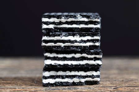 unusual color black waffles with white milk and cream filling, close-up of sweet delicious food made Standard-Bild