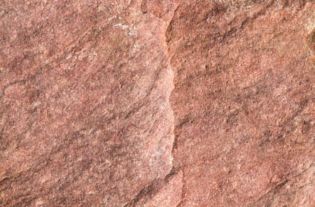 the structure of the natural broken into pieces of red stone with hollows and uneven surface, close-up of one stone with damage Archivio Fotografico