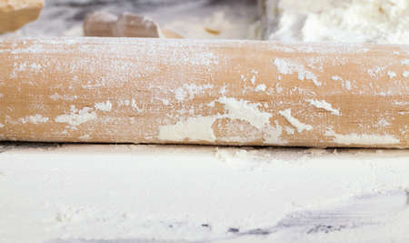 white wheat flour on a wooden table, is the ingredients for cooking durum wheat food together with a wooden rolling pin Banco de Imagens