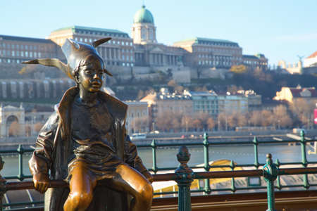 boy sitting: Budapest Attractions. Little Princess perched by the tram rails on the Pest, with Buda Castle in background, landmark of Hungary capital city. Budapest, Hungary.