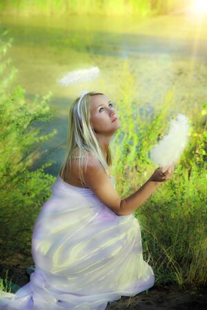 beautiful angel girl with magic fan in forest