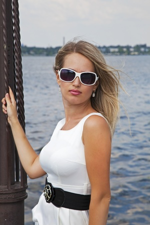 Beautiful blond girl in white dress near the river on summer