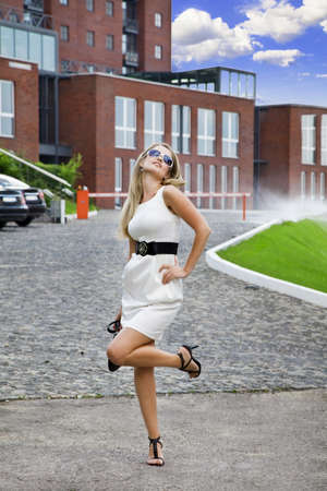 Young businesswoman in white dress in city