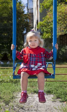Adorable little girl having fun on a swing Stock Photo