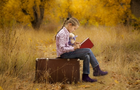 Little girl is reading a book in autumn wood