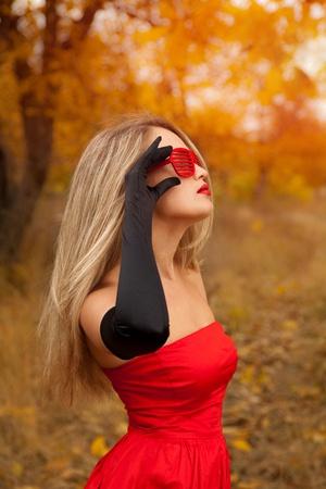 Beautiful woman in red dress in autumn
