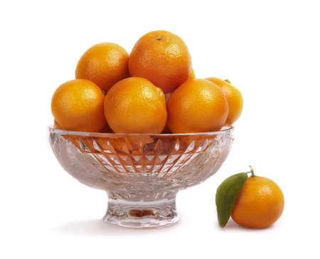 Fresh ripe mandarins in crystal vase isolated on white