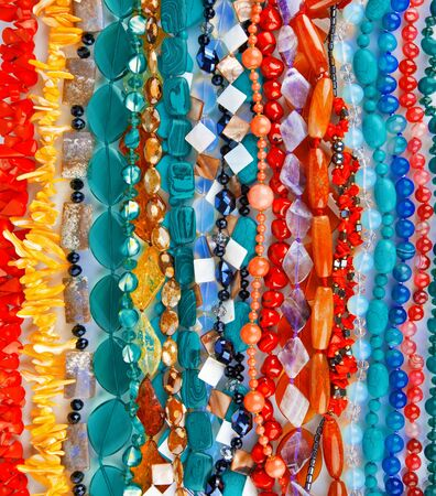 Lot of colored beads from different minerals and stone background photo