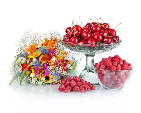 fresh raspberries, red cherries in glass bowl and beautiful colorful flowers
