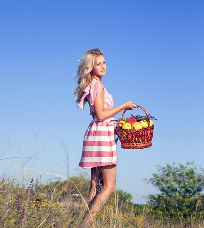 Beautiful blonde woman in the garden with apples in basket outdoor in summer day on blue sky background photo