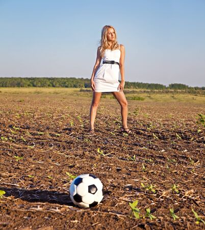 Beautiful elegant woman in white dress with Football ball on field in summer day  photo