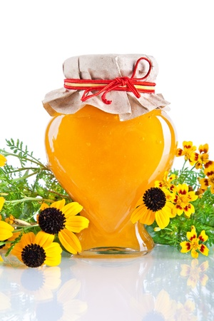 Sweet honey in jar and yellow flowers isolated on white  Stock Photo