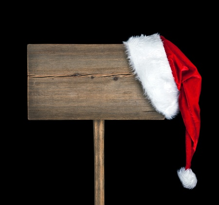 Wooden road sign with Santa hat isolated on black background