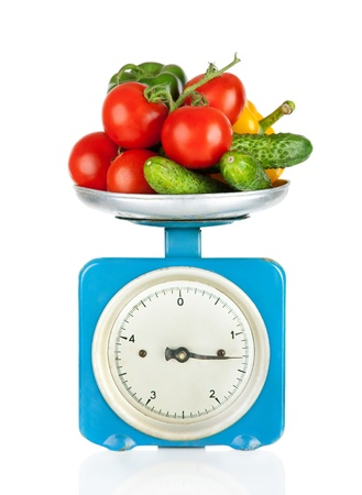 Healthy eating  Kitchen scale with vegetables isolated on white photo