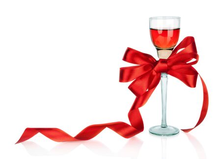 Wine in wineglass and red satin gift bow, isolated on white