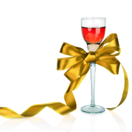 Wine in wineglass and golden satin gift bow, isolated on white photo