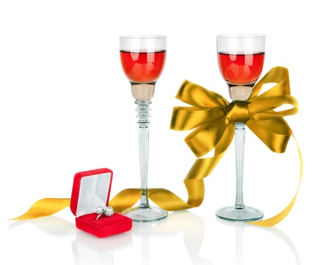 Wine in two wineglasses with golden satin  bow and wedding rings in red gift box isolated on white background