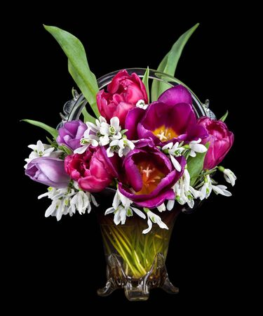 Vase of Beautiful Tulips flowers and snowdrops isolated on black background photo