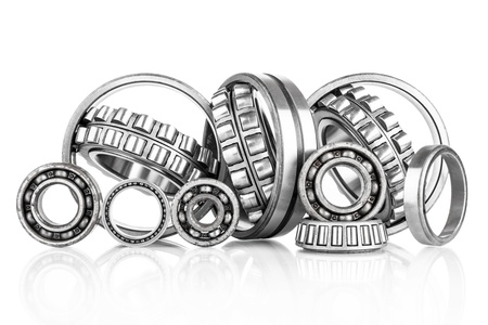 heavy industry: Composition of steel ball roller bearings in closeup isolated on white background