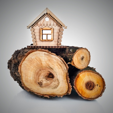 forsale: Wooden model of house and stack of wood. Concept Stock Photo
