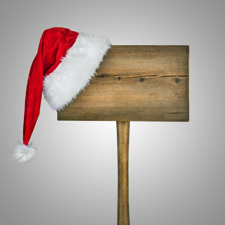 wooden road sign with Santa  hat isolated on a white  photo