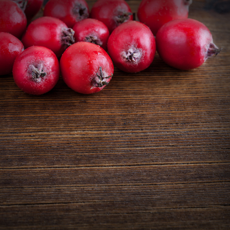 Red hawthorn berries on wooden