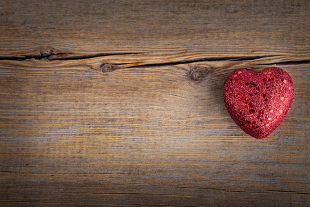 Christmas concept (decoration). Red  heart over rustic wooden background (texture) close up, horizontal. Retro Styled Wallpaper. Valentines Day photo