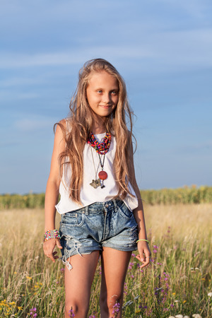 Beautiful little young fashionable hippie teenager girl in fashion clothing in a meadow  Summer day, outdoors photo