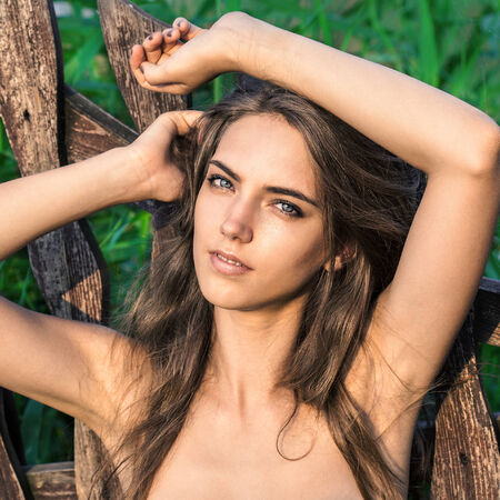 Portrait  of young pretty cute woman on green background,  summer nature. Sexy beautiful girl beauty in  forest near the wooden fence