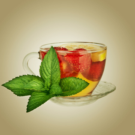 Tea cup with strawberry and mint leaf photo