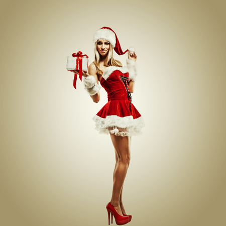 Beautiful woman in Santa Clause costume with Christmas gift. Winter portrait of sexy girl with copy space. Attractive new year and xmas party lady