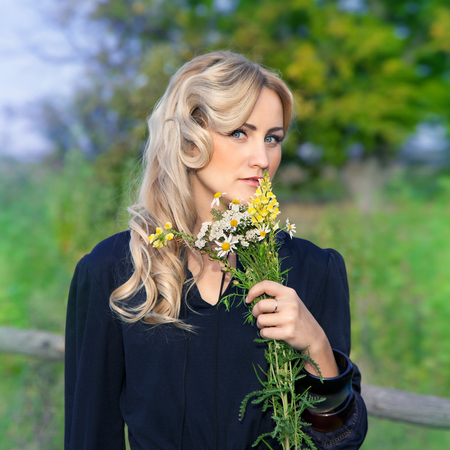 portrait of beautiful blond woman with bouquet of bright wildflowers camomile, outdoors