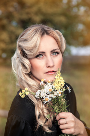 felicity: portrait of beautiful blond woman with bouquet of bright wildflowers camomile, outdoors