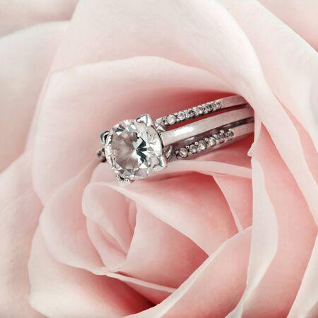 nestled: Pink Rose and diamond ring nestled inside. Macro closeup Stock Photo