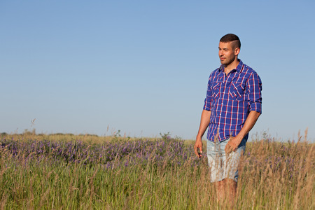 Attractive young man standing in a field