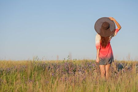 looking at view: Romantic young woman in hat standing with her arms raised to her head enjoying looking view of meadow on hot summer day