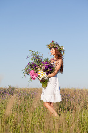 Portrait of Young beautiful Woman with Bouquet, wearing a Wreath of wild flowers