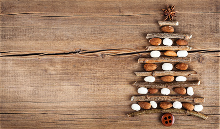 mixed marriage: Christmas card with natural decorations on wooden background. Set of different varieties of objects in the form of a tree. Winter holidays concept