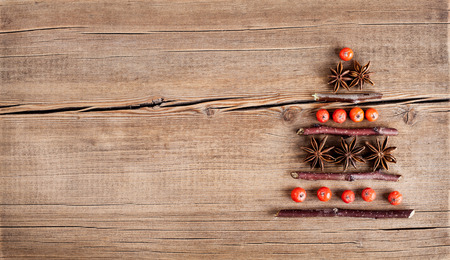 winter tree: Christmas card with natural decorations on wooden background. Set of different varieties of objects in the form of a tree. Winter holidays concept