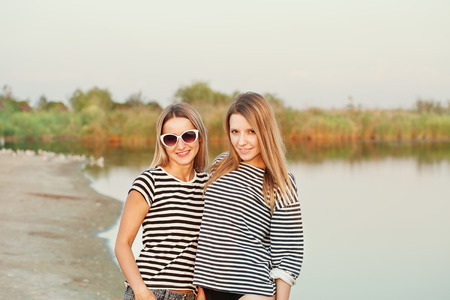 Two attractive cute smiling woman on the beach. Pretty beautiful young happy girlfriends near river. Adorable girls wearing sexy sea sailor T-shirt in summer day, outdoors Stock Photo