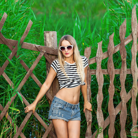 Fashion portrait of young pretty cute blonde girl. Beautiful woman posing on green background in summer day, outdoors