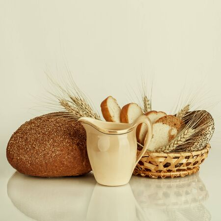 Fresh bread and wheat on the wooden table. Food background