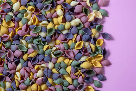 Pasta Conchiglie Rigate, mix of colorful uncooked shells with spinach and tomatoes. Textured Italian food background concept. Top view flat lay close up copy space