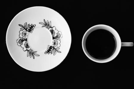 Saucer on a black background. White cup with coffee on a black background.