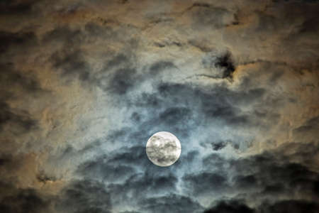 Full moon in the clouds. Artistic sketch of the dramatic night sky.