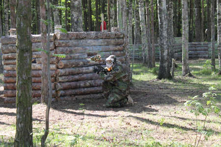gunfire: Paintball. Shooting competition of weapons with paint balls. Forest tournament.