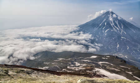 lejano oriente: Mountains and volcanoes. Beautiful landscape of Kamchatka Peninsula: summer panoramic view of Mountain Range Vachkazhets, mountain lake and clouds in blue sky on sunny day. Eurasia, Russian Far East, Kamchatka Region. Foto de archivo