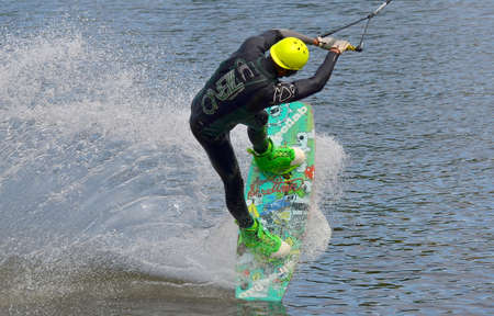 Water snowboard. The athlete with snowboard hold on to the rope and the boat accelerates.