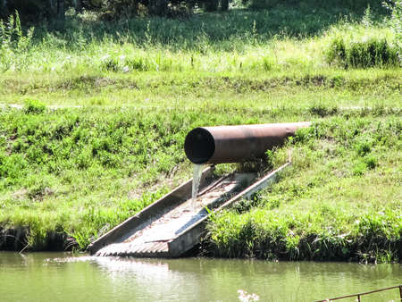 Water flows from a large pipe into the pond. Water flows from a large pipe into the pond. Stock Photo